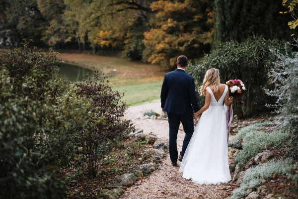 bride and groom descend garden steps of chateau lacanaud in france with back to camera