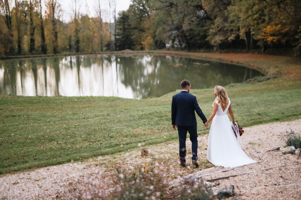 bride and groom hold hands as they cross the grass toward the lake at chateau lacanaud in dordogne, France