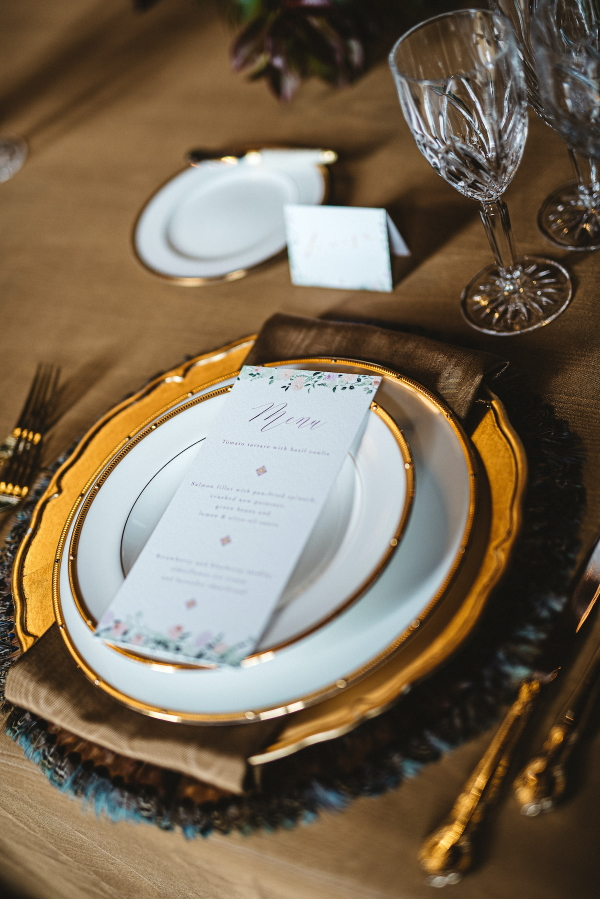 gold and blue wedding table place setting with menu on gold rimmed plate