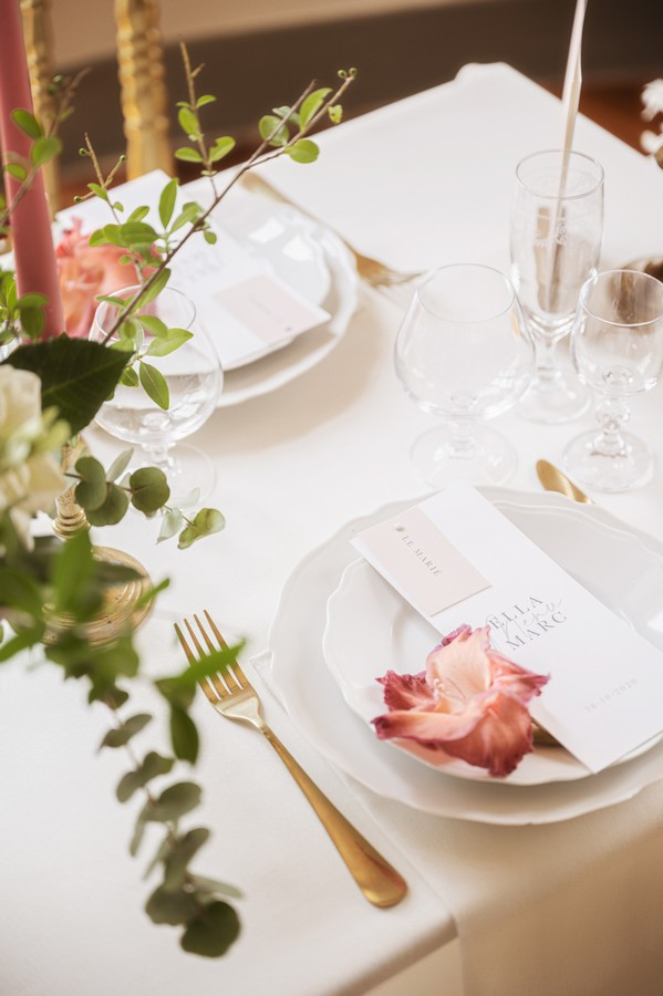 white wedding stationery on white plate with accents of pink flowers and candles