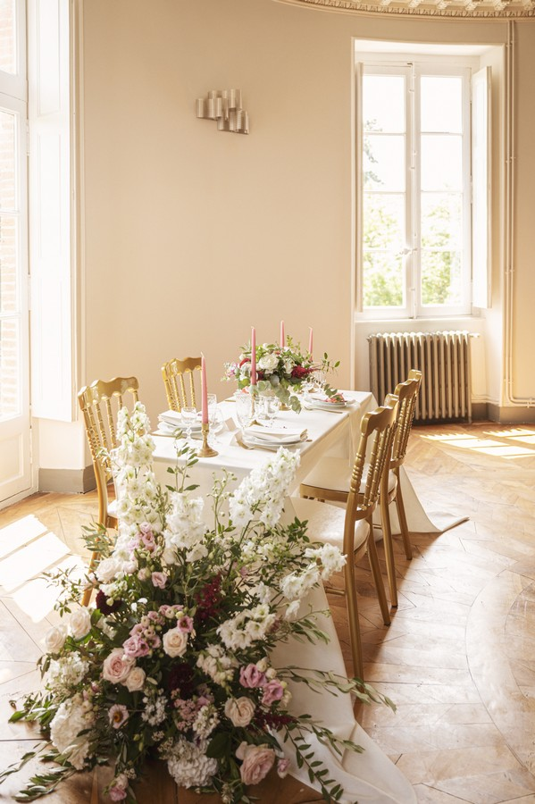 4 seat wedding table with gold chairs, pink candles and large floral arrangement at head of table