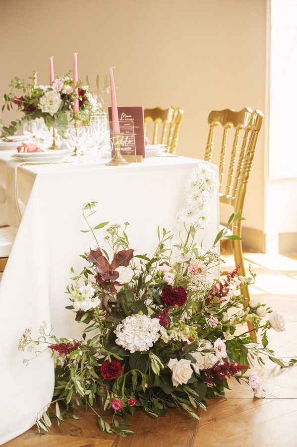 wedding table with white and burgundy flowers and gold chairs