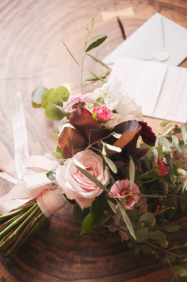burgundy, pink and white floral arrangement on old wooden tree trunk