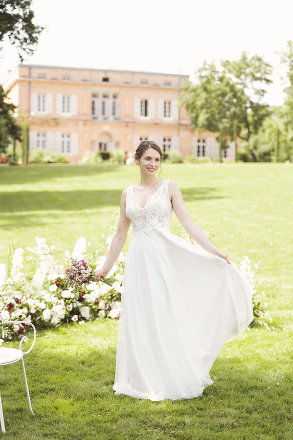 bride spins skirt on green lawn surrounded by flowers outside Chateau de Roquefoulet