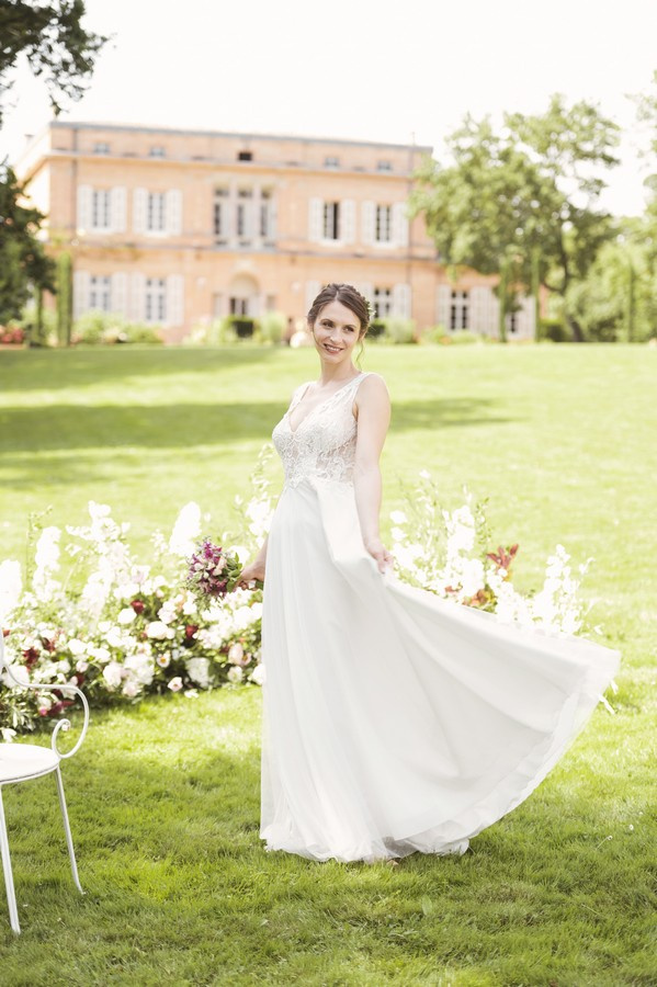 bride spins skirt of white dress with lace top