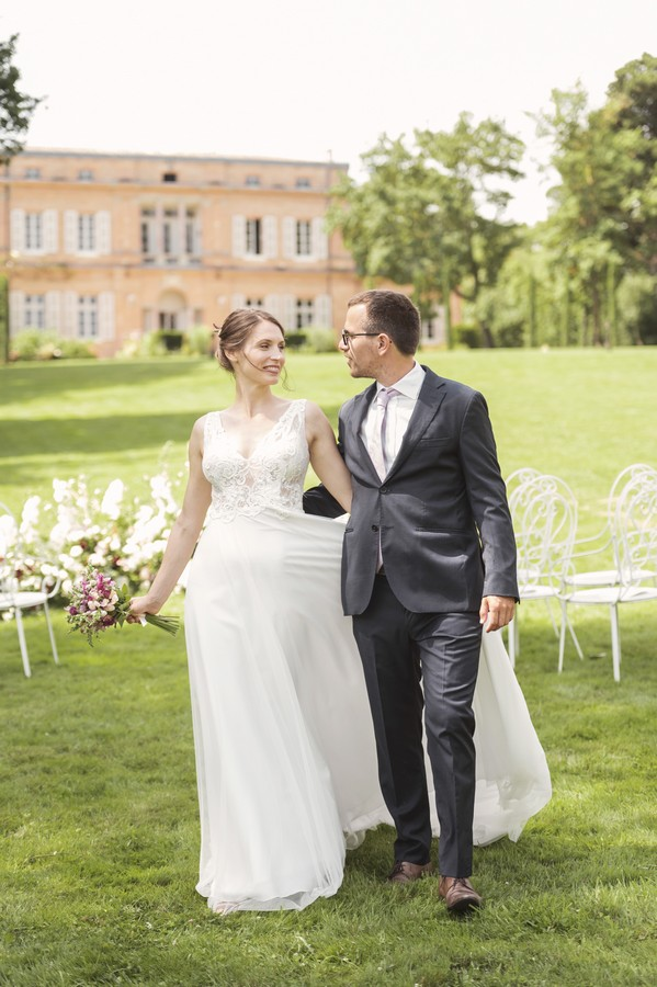bride and groom arm in arm on the lawn of french chateau
