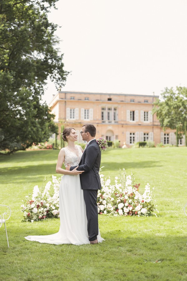 bride and groom on green lawn of french chateau