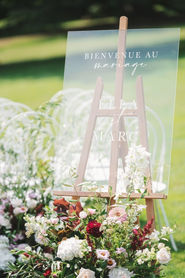 clear perspex wedding welcome sign on easel surrounded by flowers