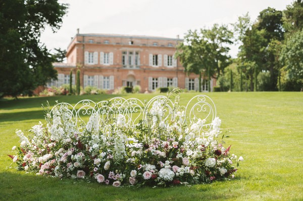 view of french chateau up grass hill behind floral arrangement and garden chairs