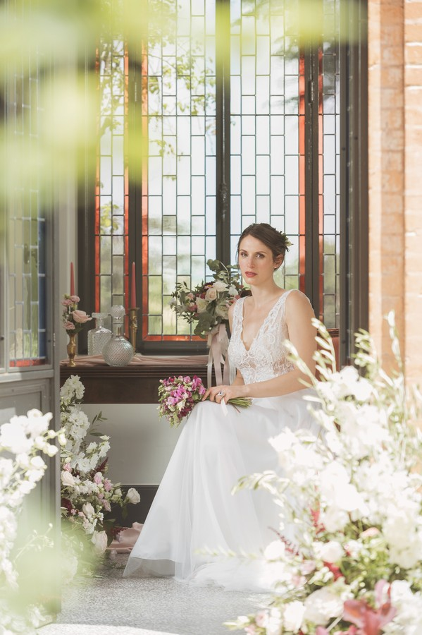 bride seated holding pink posie in front of dark wood bay window