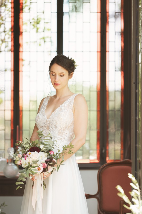 bride looks down and holds bouquet in front of dark wood bay window