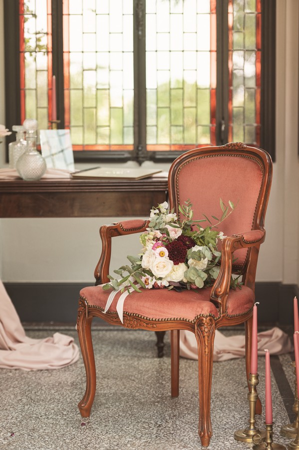 ornate maroon chair with bouquet on seat in front of bay window