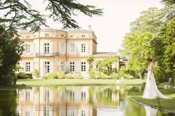 bride outside french chateau looking into still lake water surrounded by green trees