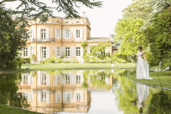 bride by lake outside french chateau which is reflected on water