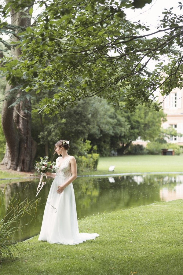 bride in white lace dress in front of lake outside Chateau de Roquefoulet