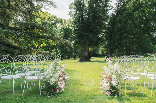 white garden chairs with flowers for wedding guests on green lawn
