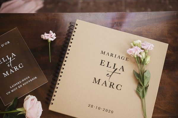 """dark wood table with pink flowers and guest book that reads """"Mariage Ella & Marc"""""""