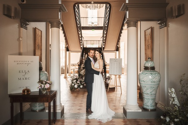 bride and groom in front of grand dark wood staircase inside entrance hall of french chateau
