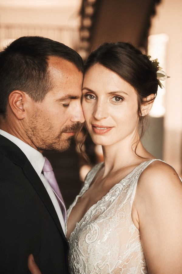 bride looks into camera and groom touches his forehead to bride's face