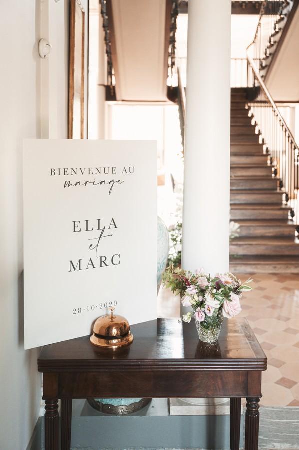 "sign by grand staircase that says ""bienvenue au mariage ella et marc"""