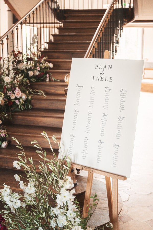"""sign by dark wood grand staircase that says """"plan de table"""" for wedding guests"""