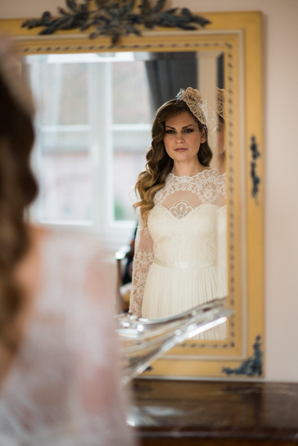 bride looks into framed mirror wearing long sleeved lace wedding dress and fascinator with netting over her face