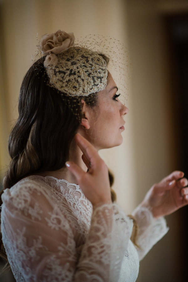 Bride fixes her hair in the mirror wearing fascinator with netting over her face