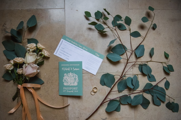 flatlay of green and gold wedding stationery surrounded by green foliage
