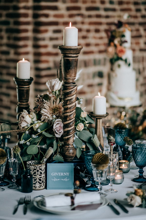 tall golden candle holders with green and brown foliage adorning wedding table