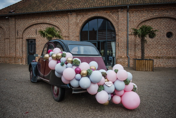 2 tone brown and black wedding car with a trail of pastel balloons