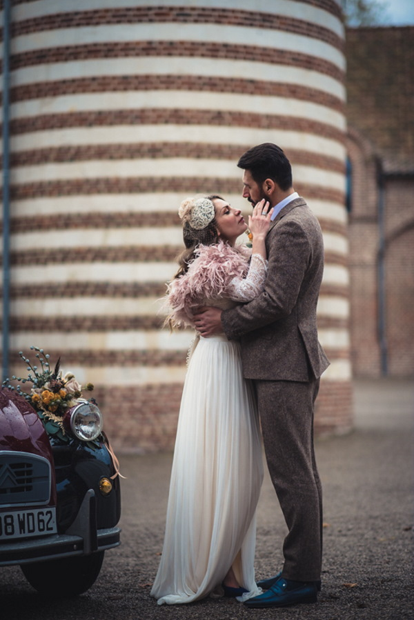 bride and groom kiss in 1920s inspired wedding outfits next to 2 tone bridal car