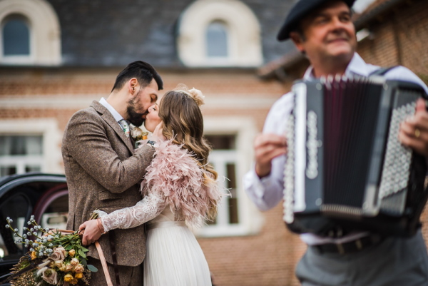 bride in pink feather boa and groom in brown tweed suit kiss next to accordion player