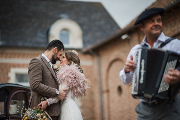 bride and groom share a kiss listening to an accordion player who is also in shot