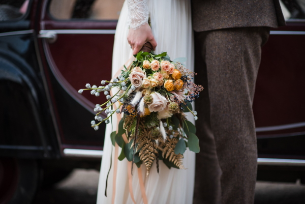 bridal bouquet hangs by brides side and includes brown, green, cream and orange flowers, berries and foliage