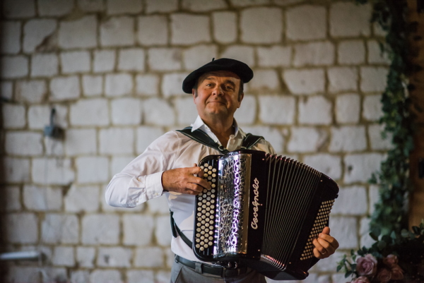 Accordion player in French beret smiles at the camera