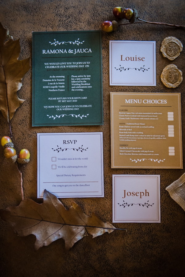 flatlay of green, gold and cream wedding stationery