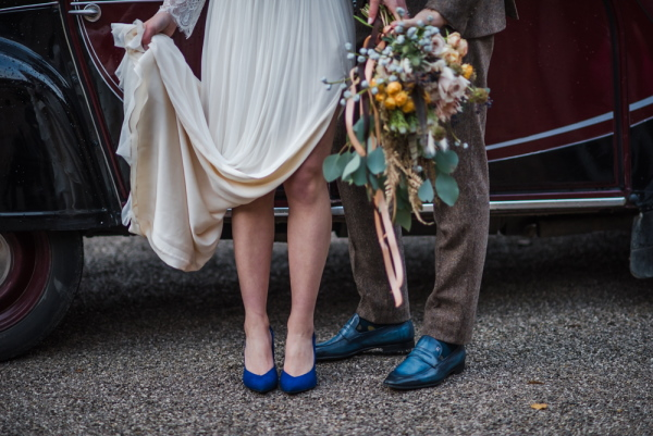 the bride and grooms feet both wearing blue shoes