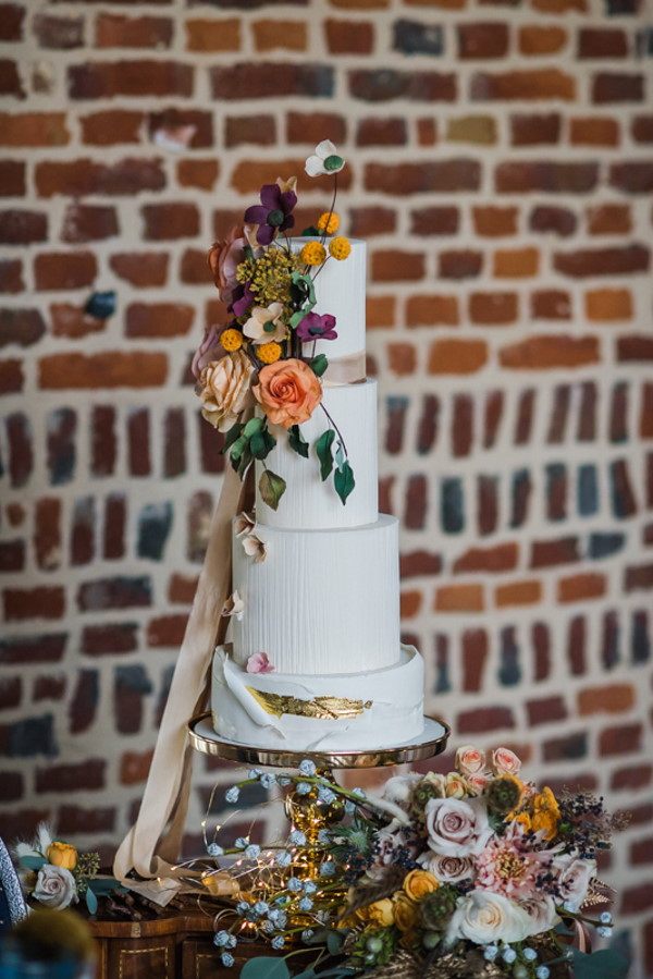 4 Tier rustic white wedding cake with orange flowers cascading down one side