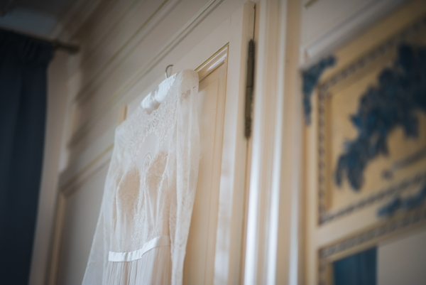 wedding dress hangs behind interior door of french chateau