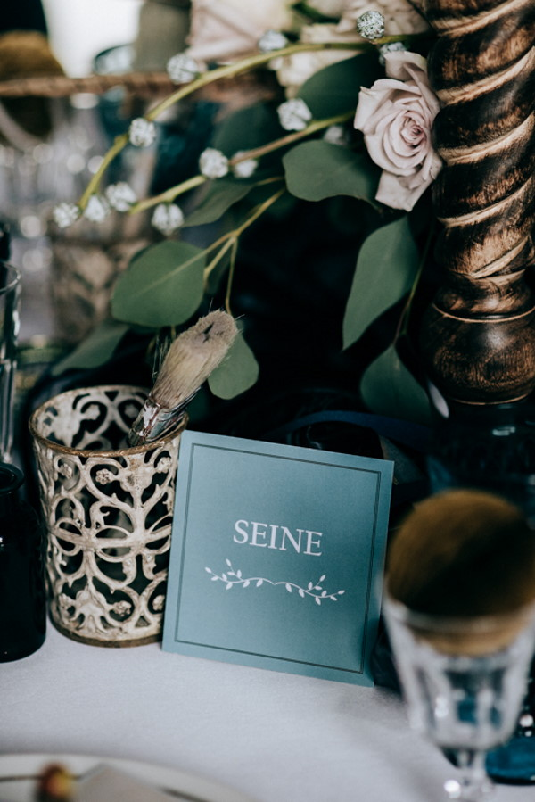 "green table name wedding stationery surrounded by green foliage that reads ""Seine"""