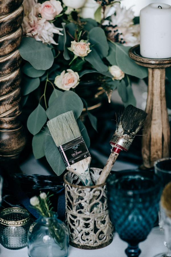 Rustic wedding decoration of green foliage and a cup of used wooden paint brushes