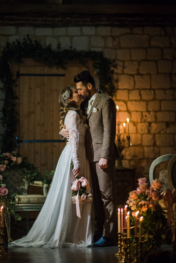 Newlywed couple kiss in candlelit rustic room surrounded by flowers