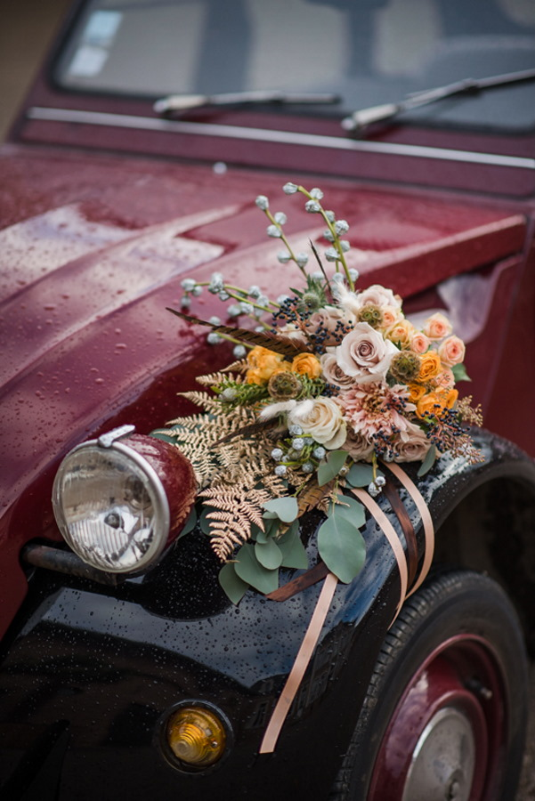 the front of 2 tone brown and black wedding car adorned with green and cream foliage