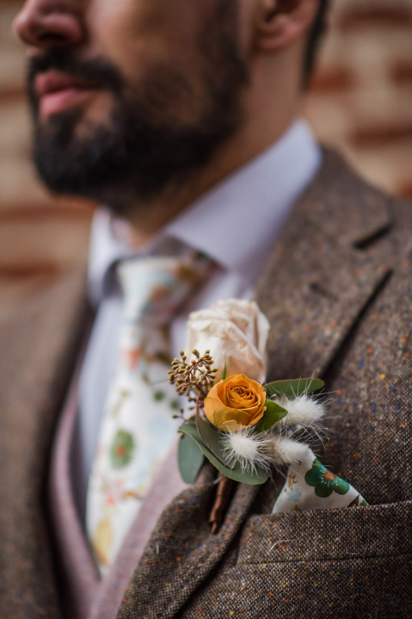 grooms buttonhole of orange an green foliage and berries on a brown tweed suit jacket