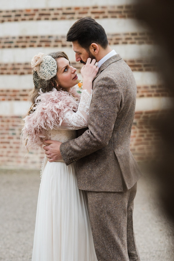 bride and groom kiss in 1920s inspired wedding outfits