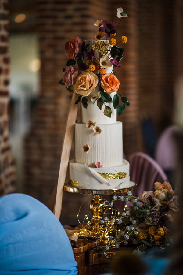 4 Tier rustic cream wedding cake decorated with fresh orange flowers