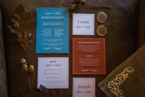 flat lay of red, green, cream and gold wedding stationery