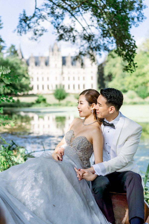 asian bride in dusty blue gown and her husband in white suit jacket sit under a tree with chateau challain visible in the background