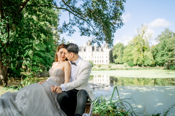 asian bride and groom sit under a tree in front of a lake with chateau challain visible in the background