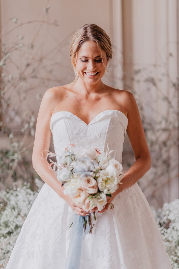 bride smiling at pastel bouquet in strapless wedding gown
